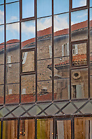 The old reflected in the windows of the new in Arles, France creates lovely abstract feel.