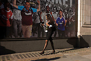 Oblivious to the gender stereotyping, a woman walks past a football-themed billboard