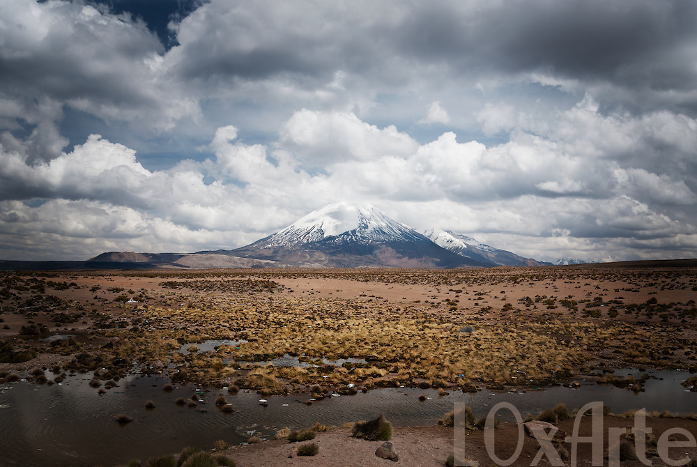Overcast day overlooking the volcanoes of Lauca National Park on the border between Chile and Bolivia, with tourist rubbish visible on the lake bed in the foreground.