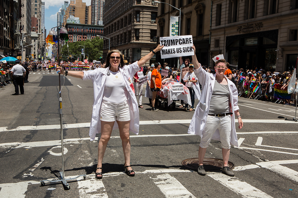 "New York, NY - 25 June 2017. New York City Heritage of Pride March filled Fifth Avenue for hours with groups from the LGBT community and it's supporters. Two women dressed as nurses, one with an IV pole, carrying a sign that reads ""Trumpcare makes us sick."""