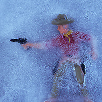 Plastic model of cowboy in ice firing his gun