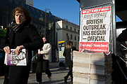On the day that the UK Government's Chief Scientific Advisor, Sir Patrick Vallance said that the Coronavirus Covid-19 outbreak was now spreading person to person in the UK, a Londoner picks up copies of the capital's London Evening Standard newspaper outside Charing Cross railway station, on 6th March 2020, in London, England.
