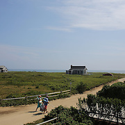 Beach goers head down a small lane to Cisco Beach, Nantucket, Nantucket Island, Massachusetts, USA. Photo Tim Clayton
