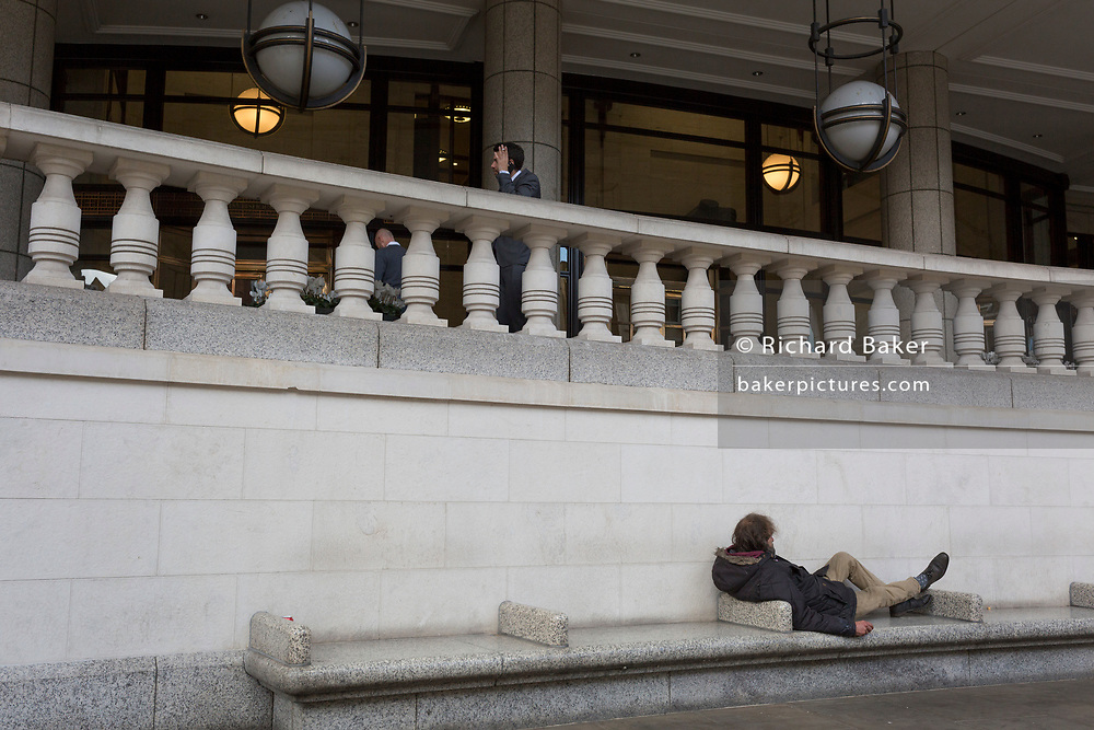 A homeless man lies on City seating as a businessman smokes above, on 14th September 2017, in the City of London, England.