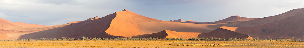 Rare storm clouds cast shadows across the massive dunes of the Namib Desert, Namib-Naukluft National Park, Namibia.