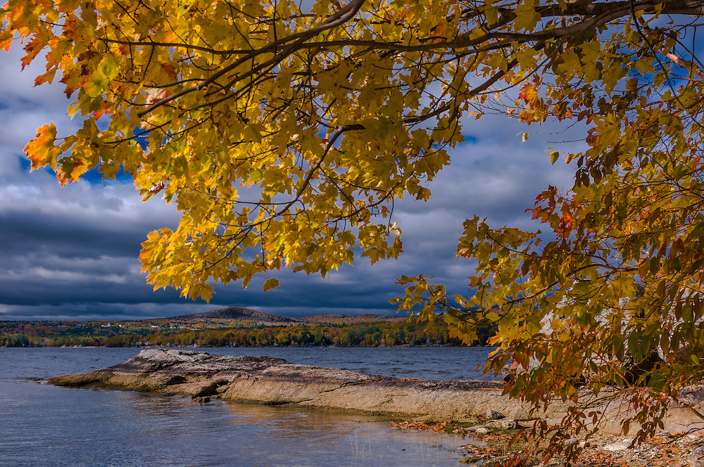 Bedrock juts out into Lake Winnisquam, framed by sugar maple trees in fall foliage, Ahern State Park, Laconia, NH