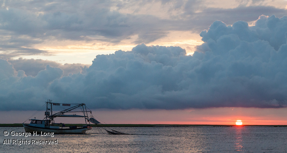 Shrimpboat trawling in the Mississippi River Gulf Outlet just after sunrise