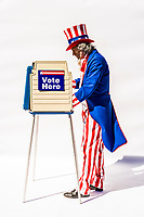 Uncle Sam at a voting booth on white background.