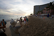 "Sunset at Waikiki Beach. Japanese tourists taking souvenir photos with the ""Pink Lady"" (Royal Hawaiian Hotel)."