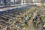 Seen from a high viewpoint, we overlook loading of roll cages at the Sainsbury's 700,000 sq ft (57,500sq m) supermarket warehouse and distribution depot at Waltham Point London England. This is the largest of 10 distribution centres using an automated ordering system for receiving food direct from suppliers by truck through 170 dock doors. Long-distance vehicles depart every two minutes, 24 hours a day, 364 days a year to 80 UK stores and handling 2.5m supermarket cases a week. The temperature is just above freezing point in a series of chill, ambient and frozen chambers. Real-time ordering means that stores can obtain requested stock within hours. Food orders are conveyed (at 2 meters a second) with sorter systems that group products together, ordering them to favour the layout of specific stores, optimising how the shelves are stacked....