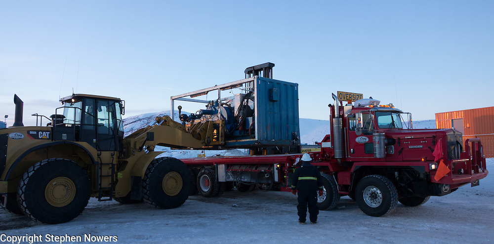 Cruz Construction employees unload a bed truck on a Linc Energy ice pad in Umiat, Alaska, during the 2013-2014 winter season. Cruz Construction provided rig support for Linc Energy's drilling program in Umiat.