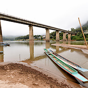 Wooden boats are tied up to bamboo poles on the sandy banks of the Nam Ou (River Ou) in Nong Khiaw in nothern Laos. In the center of frame is the high bridge spanning the river. Behind that are buildings on the waterfront. Mists shroud the steep, rocky karsts and cliffs in the surrounding terrain.