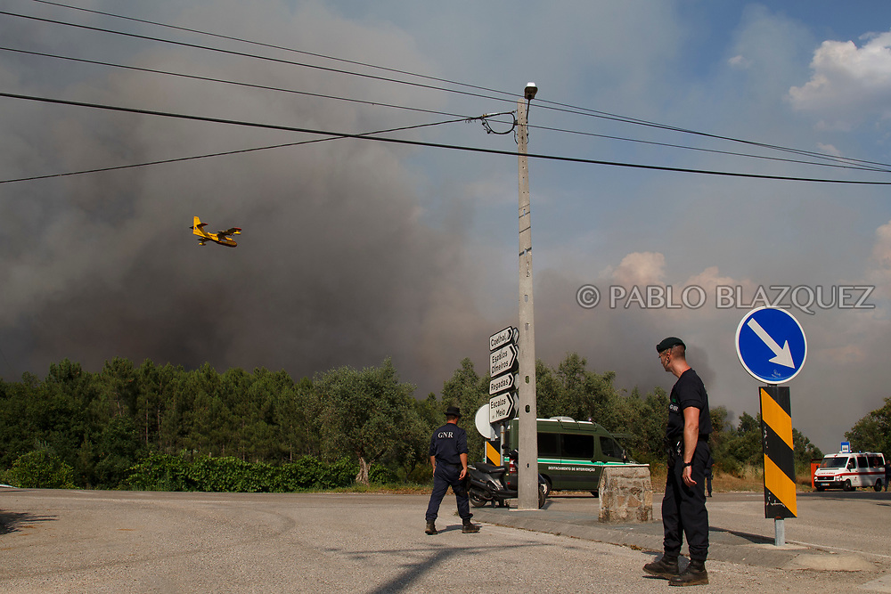 LEIRIA, PORTUGAL - JUNE 18:  Police controls the access to an area where allegedly firefighter plane crashed as a firefighter plane flies over on June 20, 2017 near Picha, in Leiria district, Portugal. On Saturday night, a forest fire became uncontrollable in the Leiria district, killing at least 62 people and leaving many injured. Some of the victims died inside their cars as they tried to flee the area.  (Photo by Pablo Blazquez Dominguez/Getty Images)