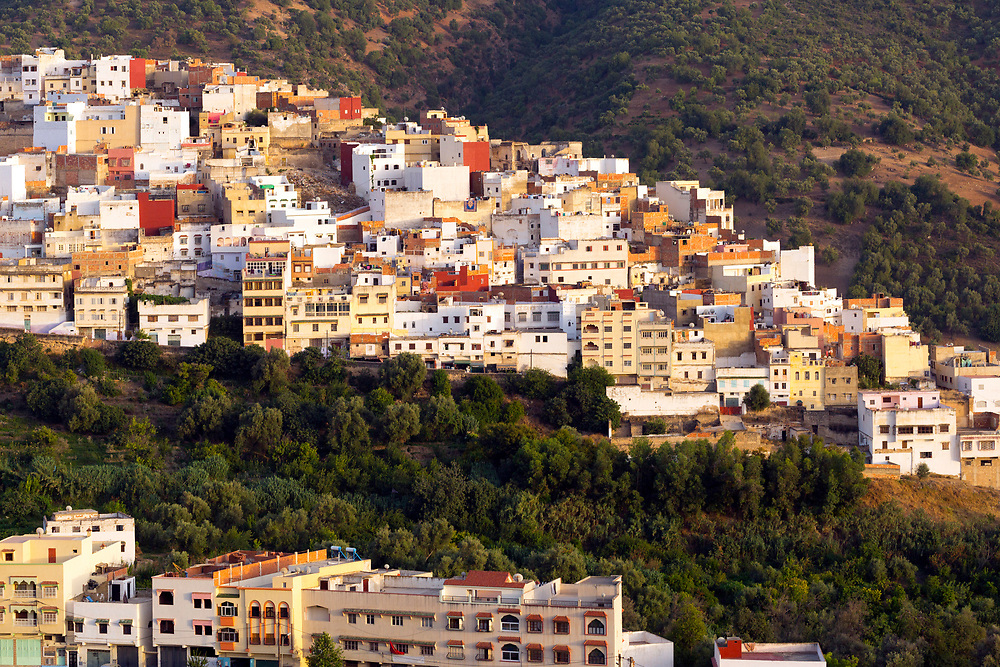 Moulay Idriss Zerhoun Medina, Middle Atlas, Morocco, 2016-06-14.<br /><br />Located nearby to Meknes and spread across the slopes of Jebel Zerhoune, Moulay Idriss holds a sacred aspect for many Moroccans; it is the burial place for Moulay Idriss the I who originally brought the religion of Islam to Morocco. The large green tiled mausoleum and mosque is located at the centre of it's Medina, which is located only 3km away from the UNESCO protected Volubilis Roman ruins.