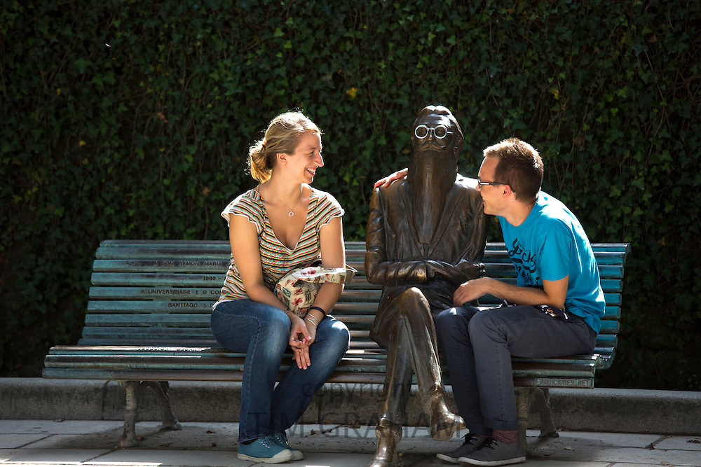 People sit on bench with bronze statue of Don Ramon Maria Del Valle-Inclan by sculptor Cesar Lombera in Alamada Park in Santiago de Compostela, Spain