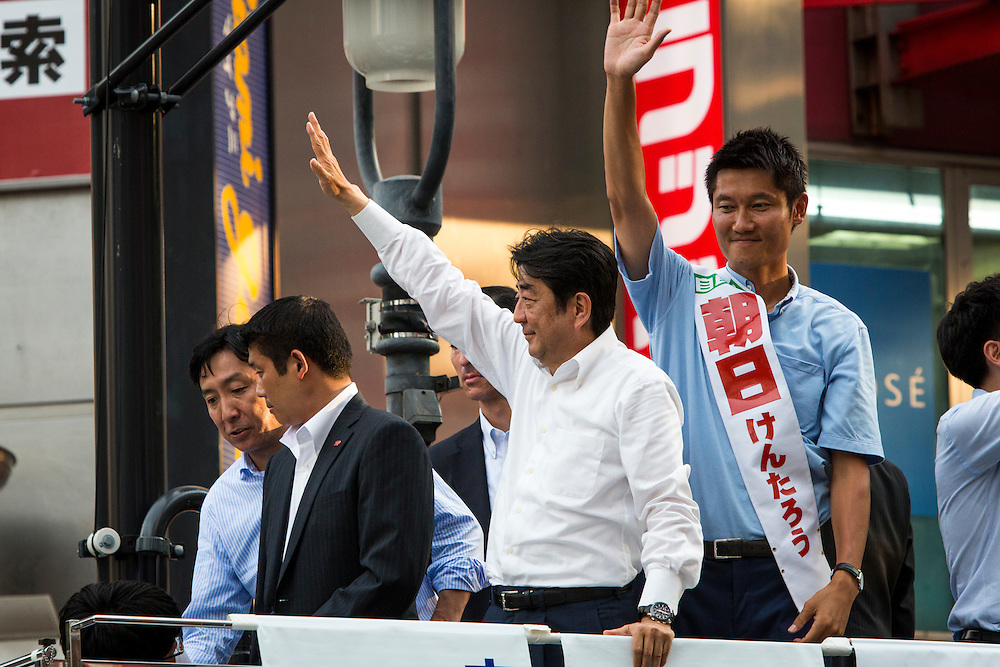 TOKYO, JAPAN - JULY 03 : Japanese Prime Minister Shinzo Abe, president of the ruling Liberal Democratic Party (LDP), and candidate Kentaro Asahi waves to their supporters during the Upper House election campaign in Shibuya crossing, Tokyo prefecture, Japan, on July 3, 2016. (Photo by Richard Atrero de Guzman/ANADOLU AGENCY)