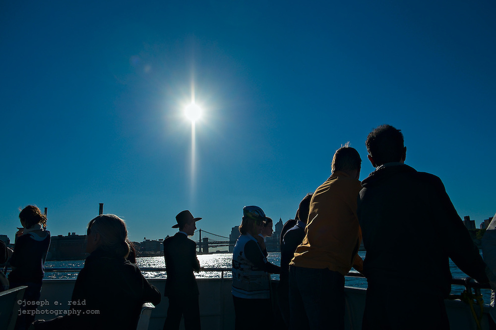 People on ferry crossing East River on clear day, New York, NY, US