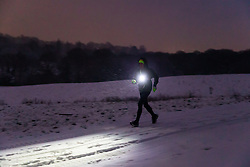 A runner makes his way across Hampstead Heath as snowfall on higher ground in London creates a wintery landscape. Hampstead, London, February 01 2019.