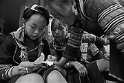 Vietnam, Sapa: young girls of ...minorities decoding a sheet of paper.