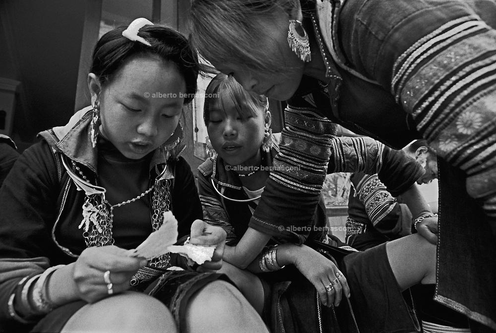 Vietnam, Sapa: young girls of ...minorities decoding a sheet of paper.
