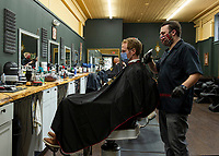 "Ross Bartlett gets a long overdue haircut from Sam ""Harvard"" Ferrante at Polished and Proper on Monday afternoon.  (Karen Bobotas/for the Laconia Daily Sun)"