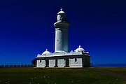 White lighthouse against saturated blue sky with silhouette of two people