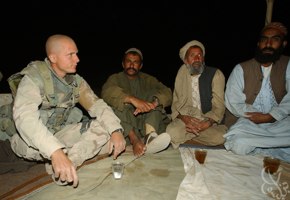 A solider with the U.S. Army  3rd Platoon 108 MP company joins local Afghan men for tea during a  May 12, 2002 evening patrol near the Kandahar airfield in southern Afghanistan. U.S. soldiers routinely patrol the area as part of the ongoing coalition Operation Enduring Freedom.