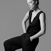 Model poses in black jumpsuit for Oliver Grace clothing design