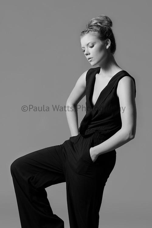 Model poses in black jumpsuit for Oliver Grace clothing design