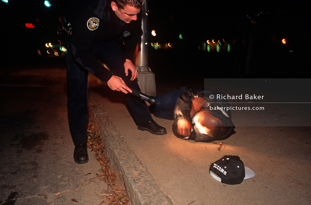 During his night patrol, a 1990s Atlanta Police Officer shines his torchlight into the face of a man lying on the ground, on 5th November 1995, in Atlanta, Georgia USA. (Photo by Richard Baker / In Pictures via Getty Images)