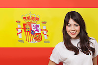 Portrait of smiling mixed race young woman against Spanish flag