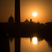 WASHINGTON, DC--The rising sun reflects off the still waters of the Reflecting Pool. At left is the US Capital Dome and the lower part of the Washington Monument.