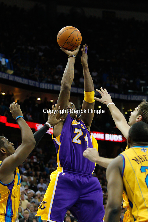 February 5, 2011; New Orleans, LA, USA; Los Angeles Lakers shooting guard Kobe Bryant (24) shoots over New Orleans Hornets defenders during the fourth quarter at the New Orleans Arena. The Lakers defeated the Hornets 101-95.  Mandatory Credit: Derick E. Hingle