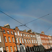 A Rainbow over Red Bricked Dublin buildings on Harcourt Stret in Dublin city, with the Tram lines of the Luas visible in the foreground