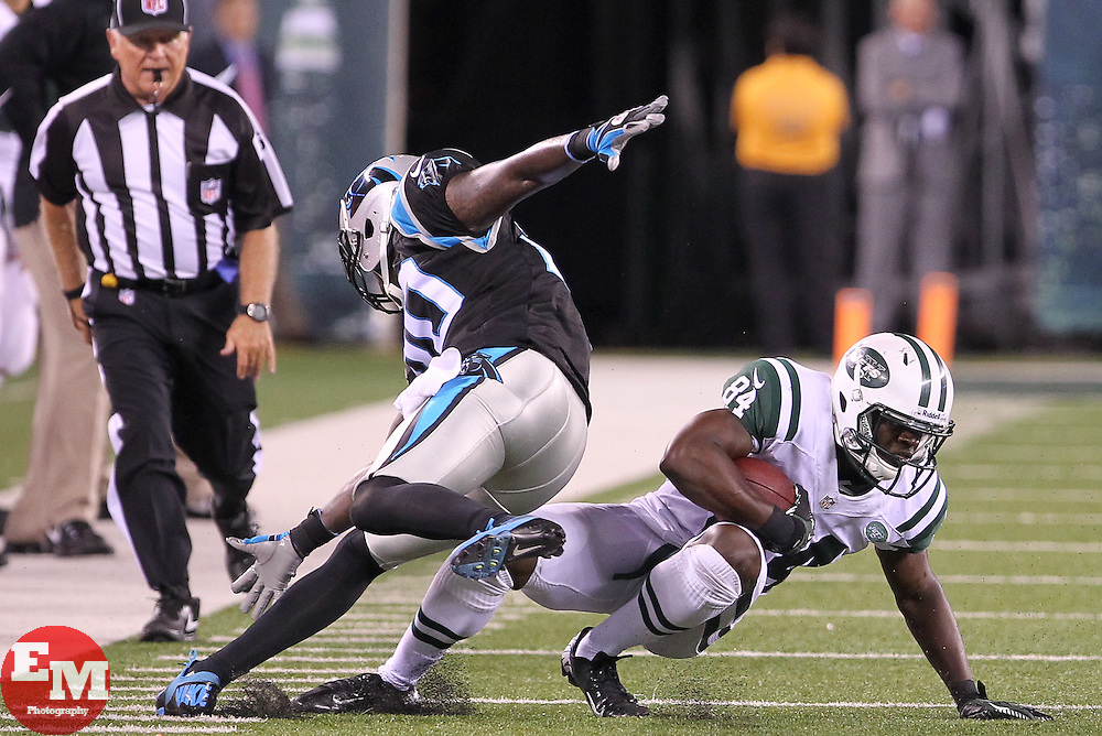 Aug 26, 2012; East Rutherford, NJ, USA; New York Jets wide receiver Stephen Hill (84) avoids a tackle by Carolina Panthers cornerback Chris Gamble (20) during the second half at MetLife Stadium. The Panthers defeated the Jets 17-12.