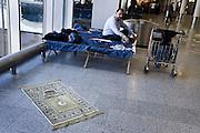 Frankfurt am Main | 18.04.2010..Durch den Ausbruch des Vulkans Eyjafjallajoekull auf Island und dadurch ausgestossene Aschewolken ist der Luftraum ueber weiten Teilen Europas f?r den Flugverkehr gesperrt, dadurch sitzen im Transit-Bereich im Flughafen Frankfurt etwa 800 Menschen fest, die kein Visum f?r Deutschland haben. Hier: Ein Muslim aus Libyen hat seinen Gebetsteppich ausgerollt und mit dem auf dem Teppich angebrachten Kompass nach Mekka ausgerichtet. ..Foto: peter-juelich.com..[No Model Release | No Property Release]