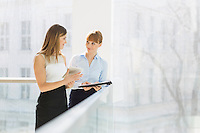 Businesswomen discussing over tablet PC while standing by railing in office