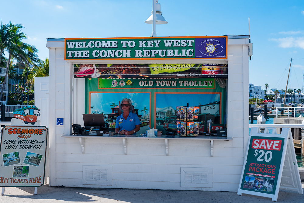 Key West, Florida--April 29, 2018. Woman in a booth in Key West selling tickets to tourist attractions. Editorial Use Only.