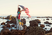 Woman by the sea holding american flag and wearing a garland of tibetan prayer flages.&quot; <br />