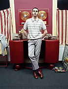 A young man standing in front of a desk with two gold records hanging above it.
