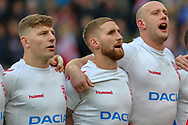 George Williams, Sam Tomkins and Chris Hill of England sing the national anthem during the Autumn International Series match at the KCOM Stadium, Hull<br /> Picture by Steve McCormick/Focus Images Ltd 07545 862647<br /> 27/10/2018