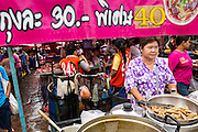 "24 AUGUST 2013 - BANGKOK, THAILAND: A soup seller in Khlong Toei Market waits for customers. She sells bowls of soup in two sizes, normal for 30Baht (about .95¢ US) and large for 40Baht (about $1.20 US). Thailand entered a ""technical"" recession this month after the economy shrank by 0.3% in the second quarter of the year. The 0.3% contraction in gross domestic product between April and June followed a previous fall of 1.7% during the first quarter of 2013. The contraction is being blamed on a drop in demand for exports, a drop in domestic demand and a loss of consumer confidence. At the same time, the value of the Thai Baht against the US Dollar has dropped significantly, from a high of about 28Baht to $1 in April to 32THB to 1USD in August.    PHOTO BY JACK KURTZ"