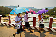15 MARCH 2013 - BAN SOMSANOUK, LAOS: School girls cross a bridge over the Nam Ou River in Ban Somsanouk near Luang Prabang, Laos.   PHOTO BY JACK KURTZ