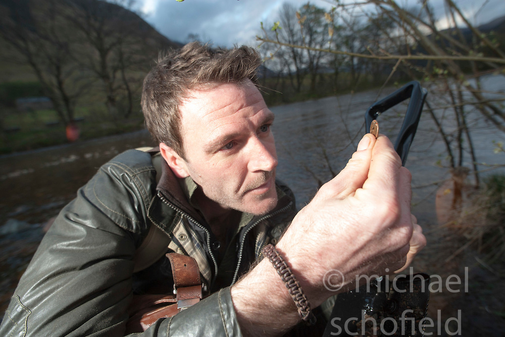 Finding a coin. Historian Ashley Cowie in a river near Fort William, during his road trip. He is doing a seven part series for The Scottish Sun on Scotland's treasure hunts at the end of April..©Michael Schofield..