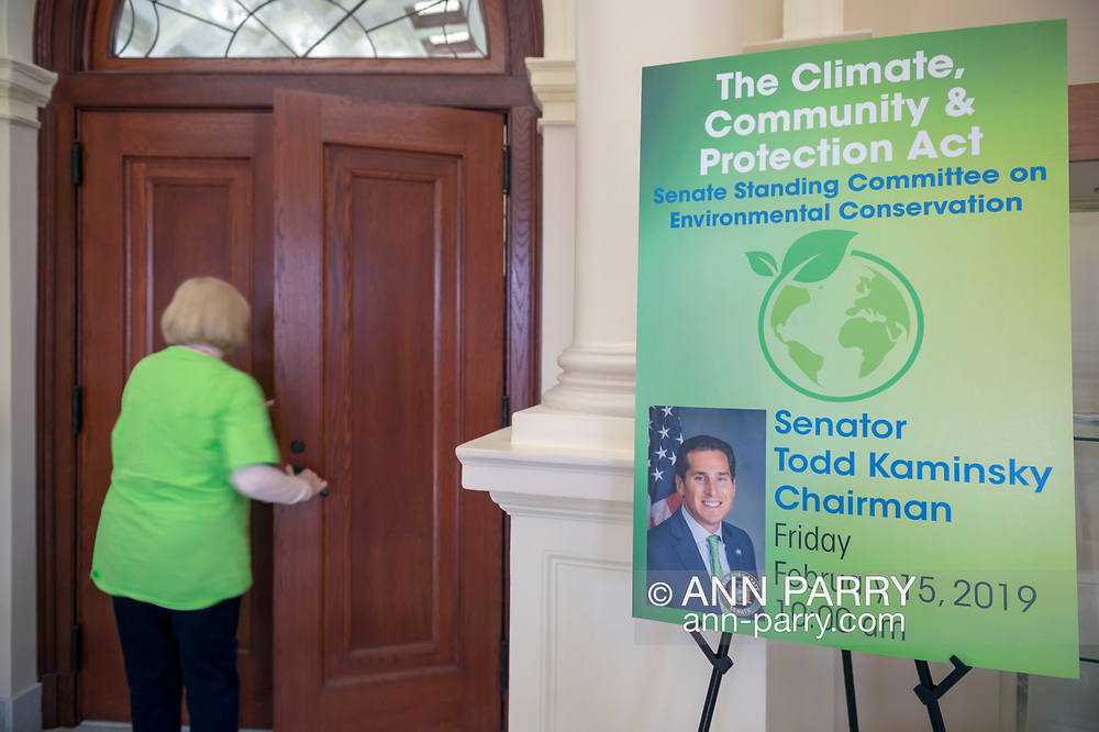 Mineola, New York, USA. 15th Feb, 2019. Activist wearing neon green Climate Emergency shirt re-enters chamber during NYS Senate Public Hearing on Climate, Community & Protection Act, Bill S7253, Sign next to entrance give info about the bill sponsored by Sen. Todd Kaminsky, Chair of Senate Standing Committee on Environmental Conservation. This 3rd public hearing on bill to fight climate change was on Long Island.