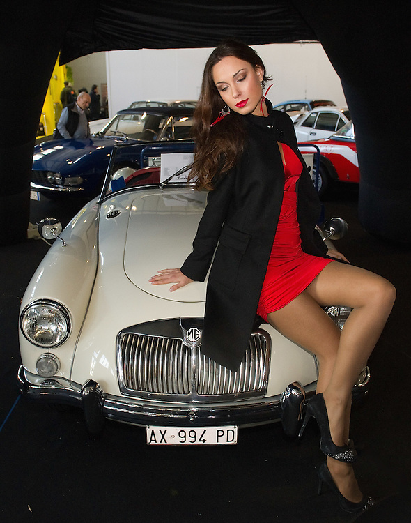 PADOVA, ITALY - OCTOBER 27:  A model poses for pictures while sitting on a vintage MG car on October 27, 2011 in Padova, Italy. The Vintage and Classic Cars Exhibition of Padova, running from the October 28 - 30, is the most important European trade show for vintage cars and motorbikes, showcasing over 1600 vehicles.