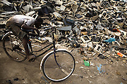 A boy sits on his bicycle near a large pile of plastic casings from computers and other electronics near the Agbogboloshie market in Accra, Ghana on Tuesday August 12, 2008.