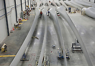 Workers check finished wind turbine blades at TPI Composites in Newton, Iowa on February 12, 2010.