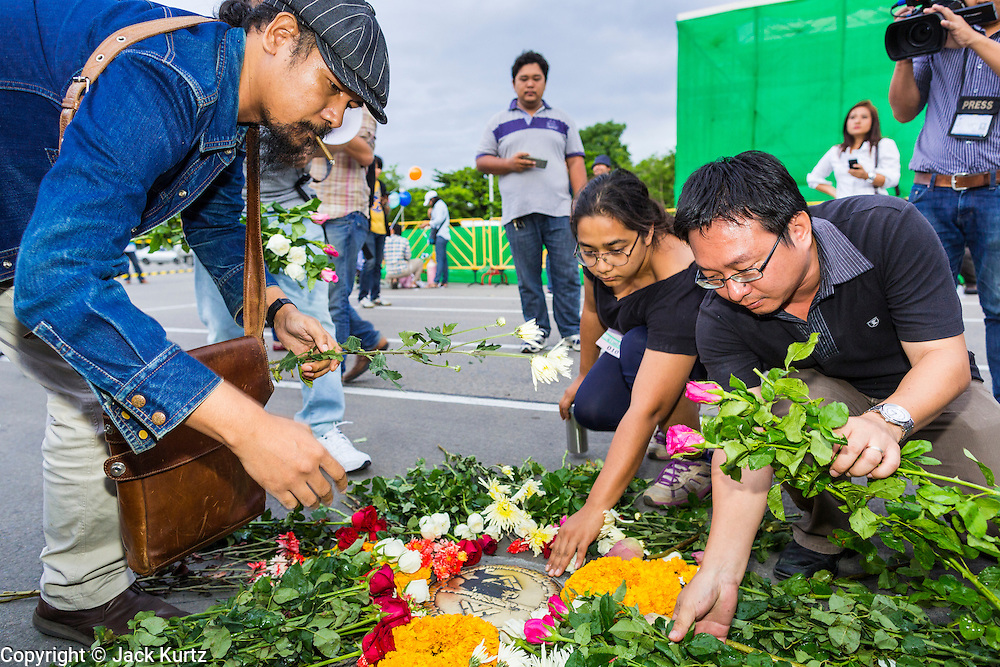 "24 JUNE 2014 - BANGKOK, THAILAND: Members of the ""Monsoon Poets Society"" lay roses at the spot where the ""People's Party"" demanded a constitutional monarchy during a bloodless coup in 1932. The poets  gathered in front of the Anantasamakom Throne Hall Tuesday to pay homage to the People's Party, a Siamese (Thai) group of military and civil officers (which became a political party) that staged a bloodless coup against King Prajadhipok (Rama VII) and changed Thailand (then Siam) from an absolute monarchy to a constitutional monarchy on 24 June 1932. Since the coup against the civilian government on 22 May, the ruling junta has not allowed political gatherings. Although police read the poems, they did not arrest any of the poets or make any effort to break up the gathering.     PHOTO BY JACK KURTZ"