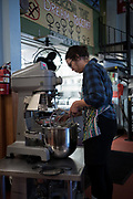 7am: Candice, on biscuit duty, negotiates the mixer. The cafe's day begins.